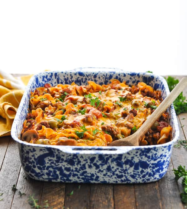 Easy comfort food dinner of Johnny Marzetti Casserole in a blue and white enamel pan with wooden spoon