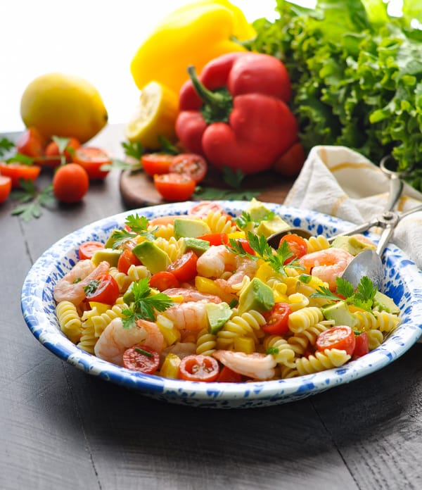 A shrimp pasta salad on a blue plate with chopped avocado and cherry tomatoes