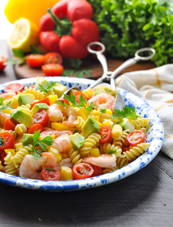 A side shot of a shrimp pasta salad on a plate with avocado and tomatoes chopped up