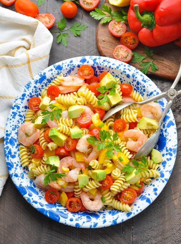 An overhead shot of a shrimp pasta salad on a blue plate with avocado, yellow bell pepper and tomatoes