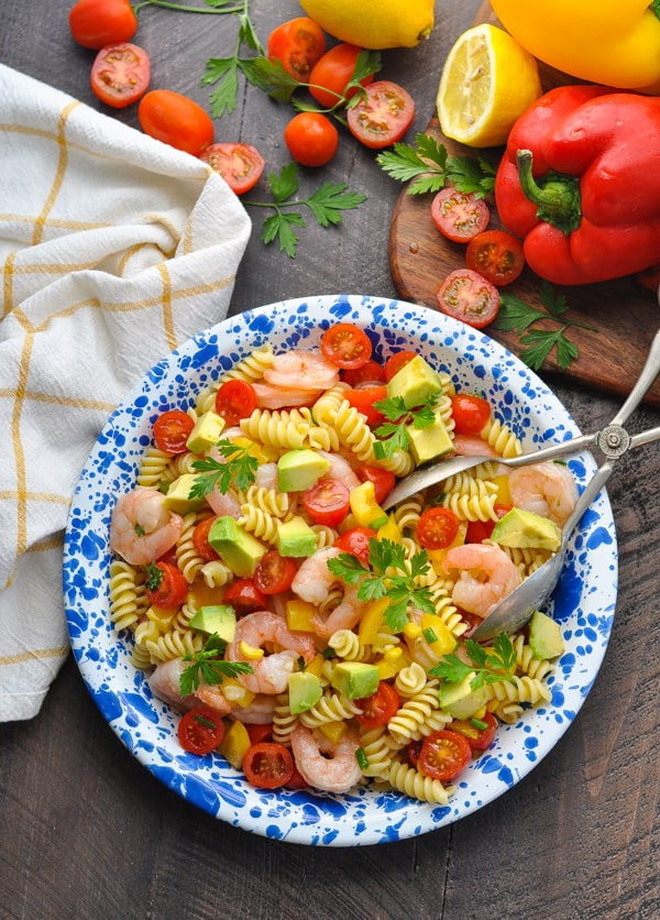 A shrimp pasta salad on a blue plate with salad tongs and chopped tomatoes at the side