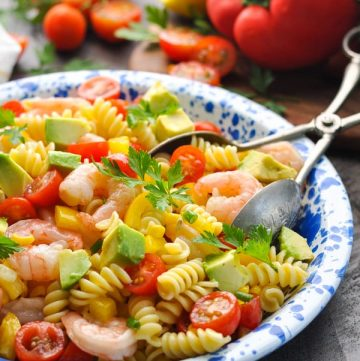 A side shot of an avocado and shrimp pasta salad on a blue plate