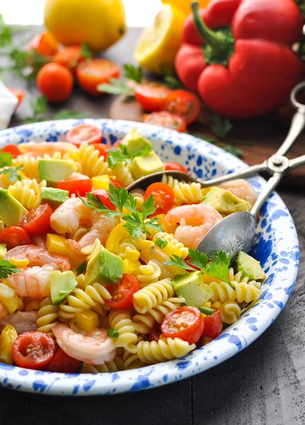 A side shot of a shrimp pasta salad with chopped bell pepper, avocado and corn on a plate