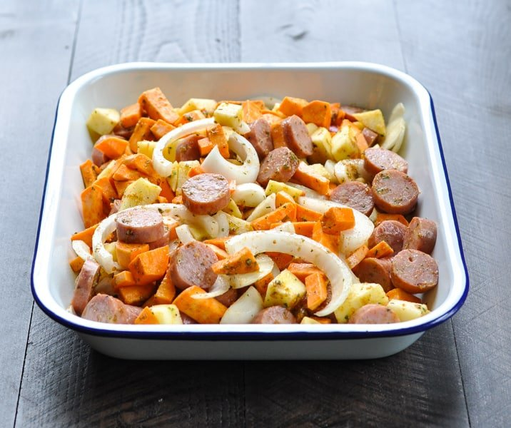 Chicken sausage and sweet potato casserole in a white baking dish before the oven