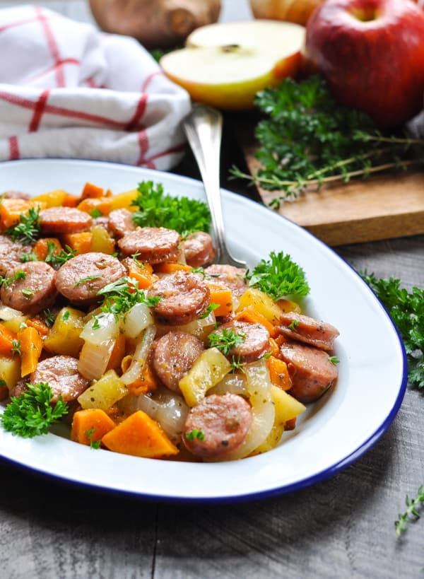 Plate of baked chicken sausage and sweet potatoes garnished with parsley