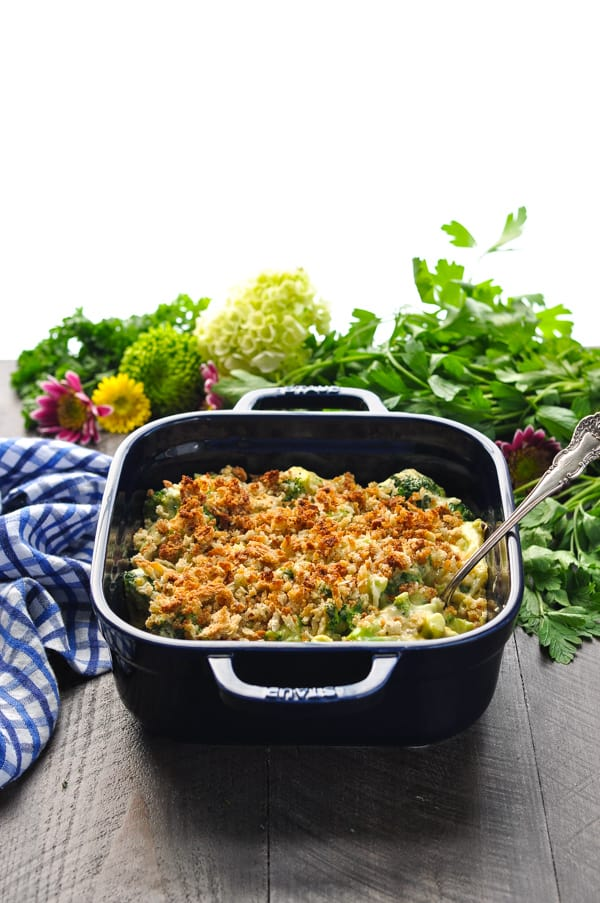 Broccoli Casserole with cheese baked in a blue dish with serving spoon