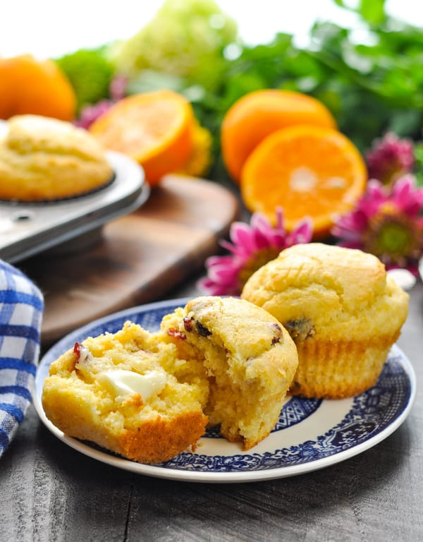 Close up of orange cranberry corn muffins on a blue and white plate with butter