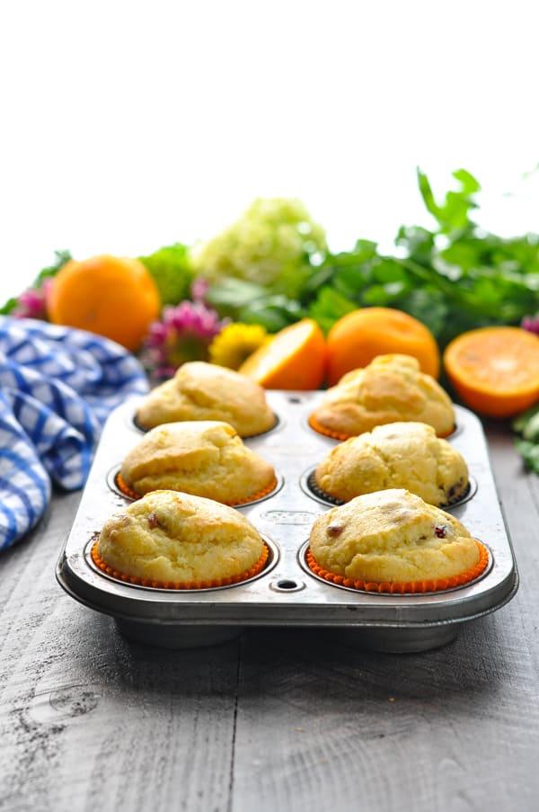 Orange Cranberry Corn Muffins in a muffin tin