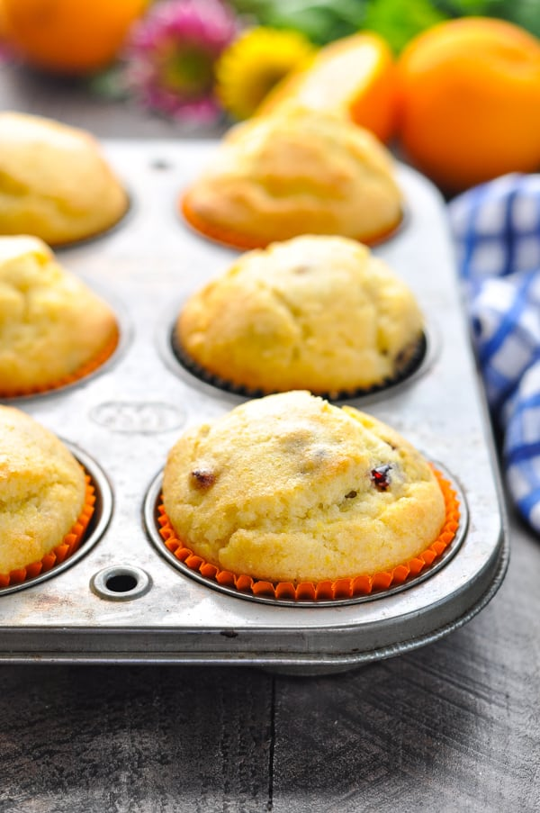 Close up of orange cranberry corn muffins in muffin tin
