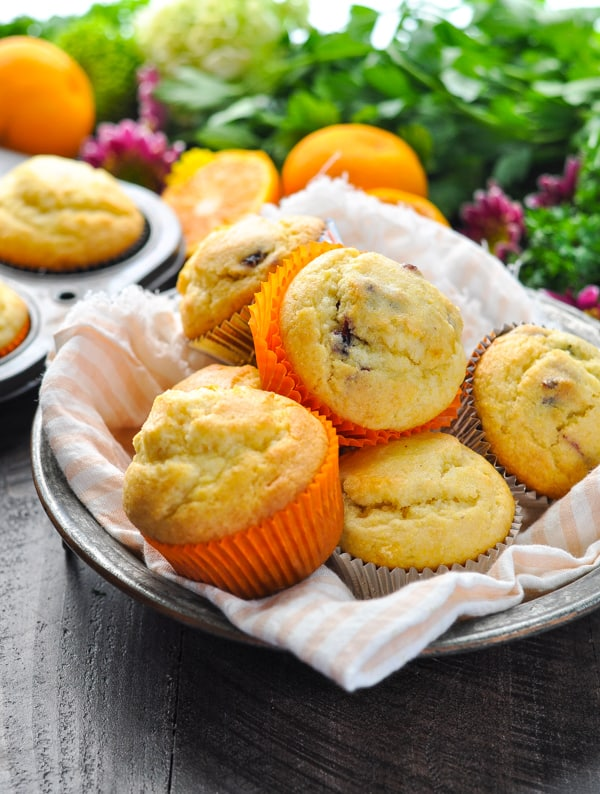 Bowl of orange cranberry corn muffins lined with a pink and white stripe towel