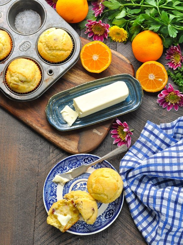 Overhead image of orange cranberry corn muffins on a plate with butter and muffins in a tin