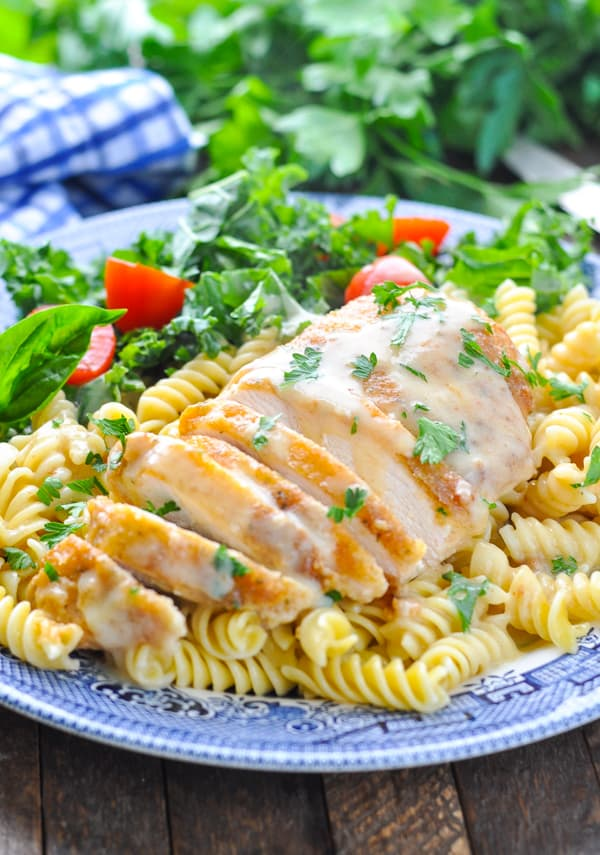 Sliced baked parmesan chicken recipe over pasta