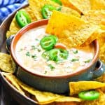 Easy queso dip from the slow cooker served with tortilla chips and jalapenos