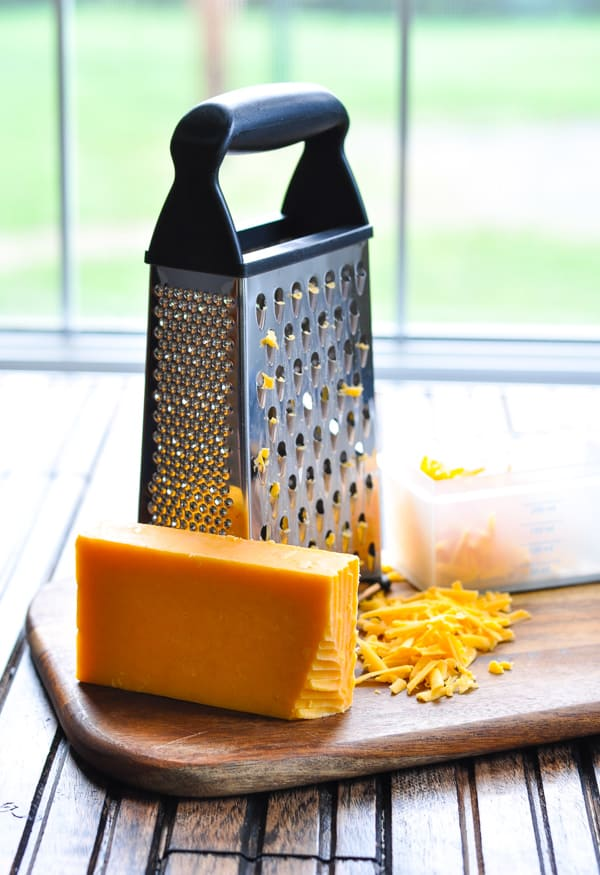 Grated cheddar cheese on cutting board