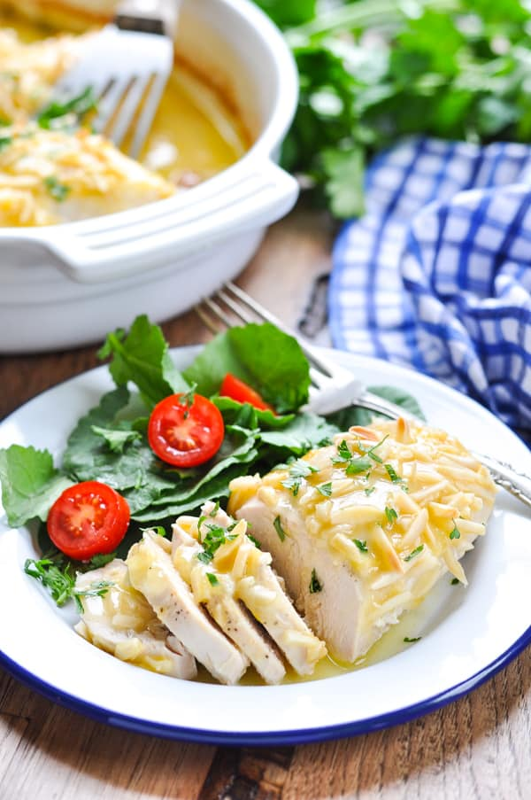 Oven baked chicken breast on a plate with salad.