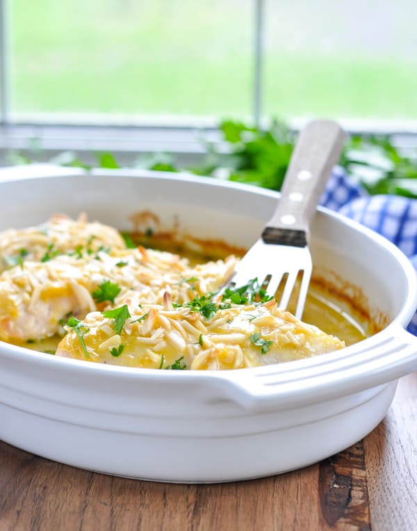 White baking dish full of oven roasted chicken breasts with a spatula for serving