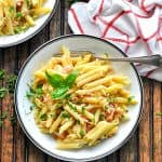 Pasta bowl full of penne with prosciutto parmesan cream sauce and text overlay