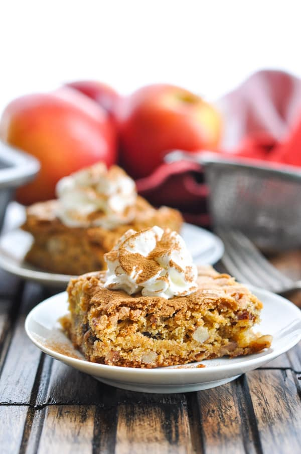 Apple Pecan Date Bar with whipped cream on a plate