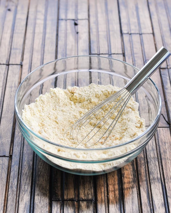 Dry ingredients for date bars in a glass bowl with whisk
