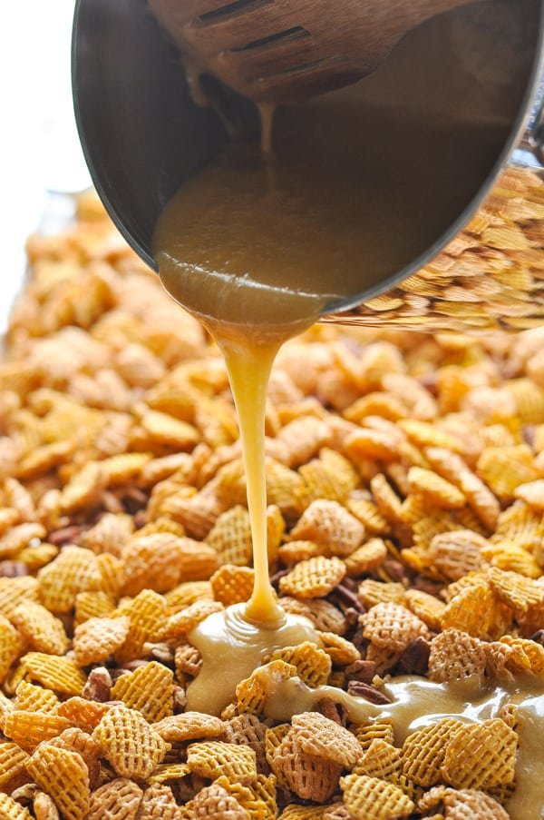 Pouring caramel sauce over Crispix and pecans