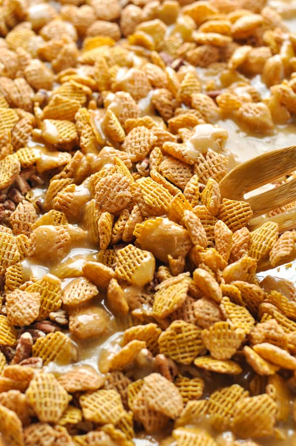Stirring cereal snack mix with caramel sauce on baking sheet