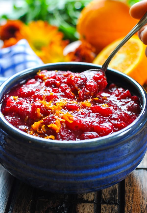 Spoon picking up cranberry orange sauce from serving bowl