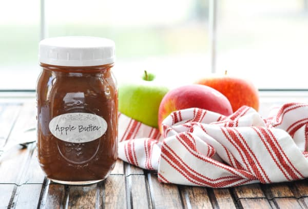 Horizontal shot of a jar of homemade apple butter with apples in the background