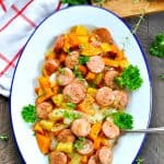 Overhead image of baked sweet potatoes with apples and chicken sausage on a serving plate with text overlay