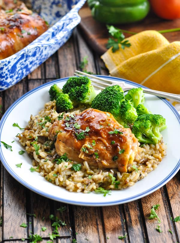 Wild rice and baked chicken thigh on a plate with broccoli