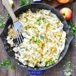 Overhead image of fried cabbage with apples and onions in a skillet with text below