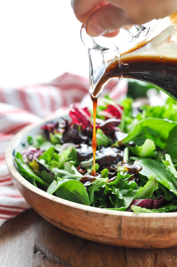 Pouring balsamic vinaigrette on salad