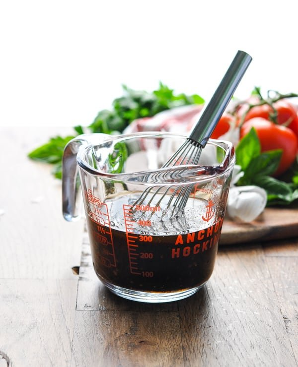 Honey Balsamic Vinaigrette in a glass measuring jar with whisk