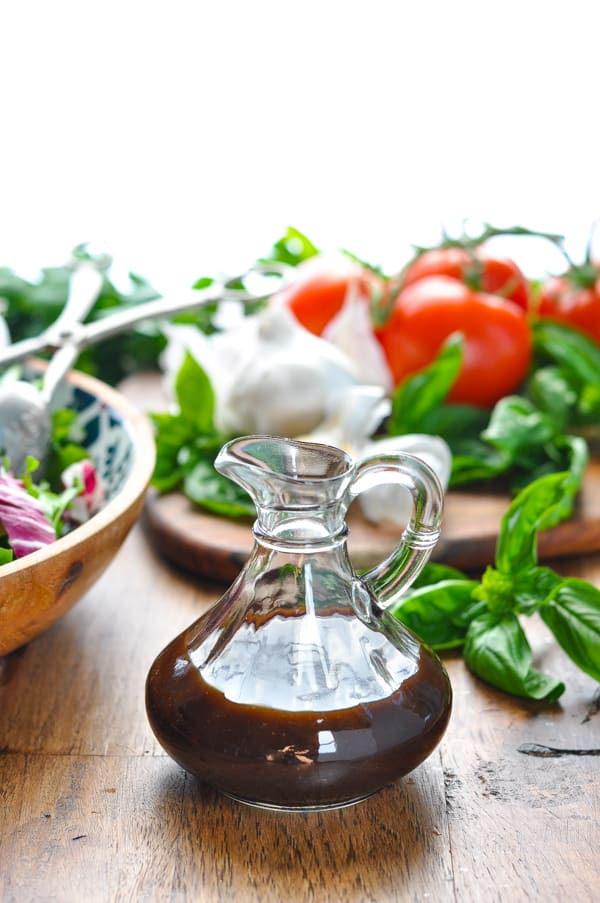 Jar of balsamic vinaigrette with fresh vegetables and herbs in background