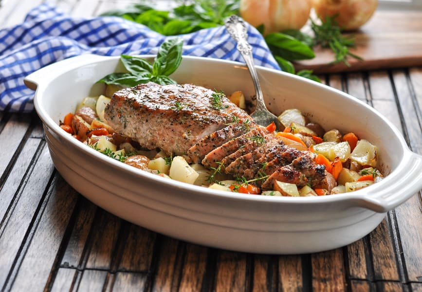 One Dish Roasted Pork Tenderloin with potatoes and vegetables in a white baking dish