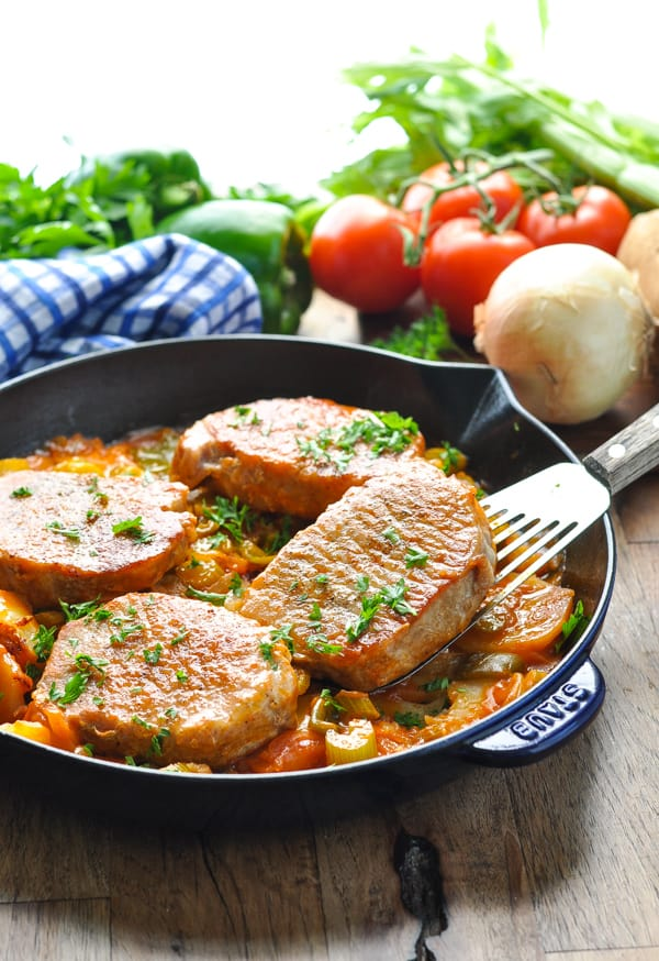 Boneless pork chops with potatoes and vegetables in a skillet