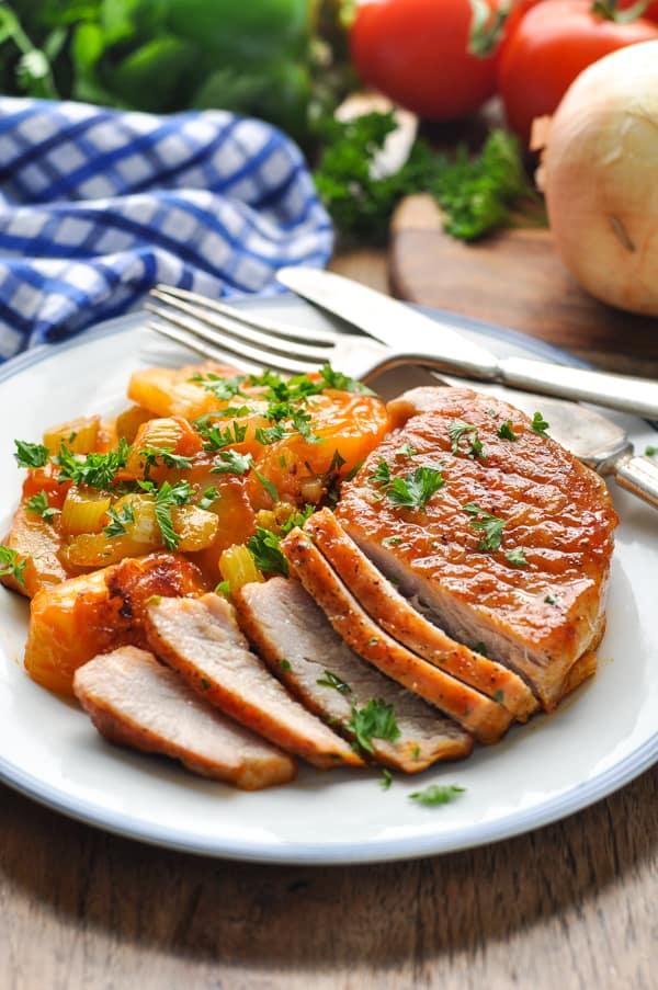Sliced boneless pork chop on a plate with vegetables