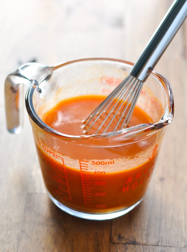Tomato sauce in a glass measuring cup with whisk