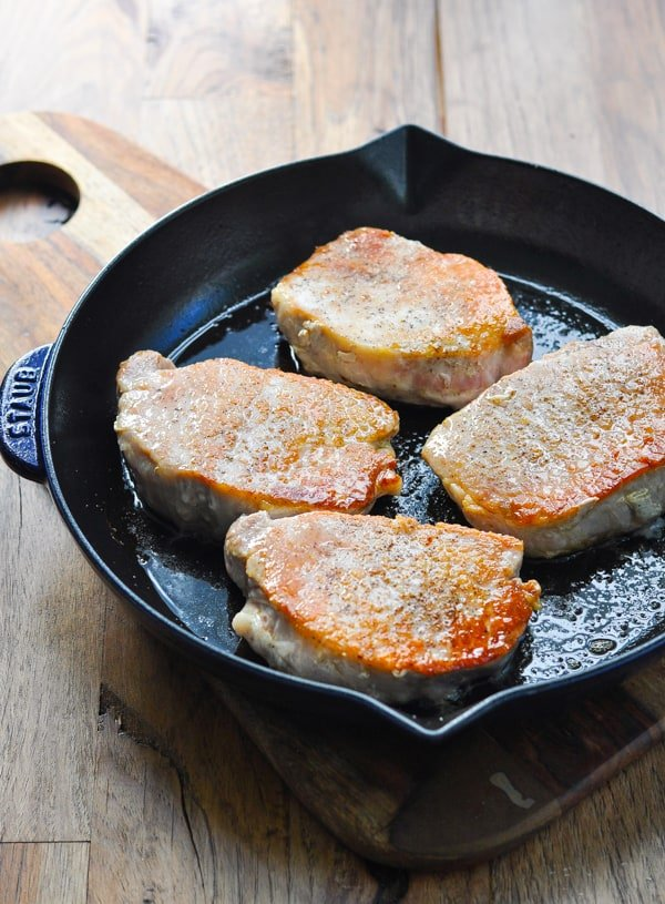 Pan fried pork chops in a cast iron skillet