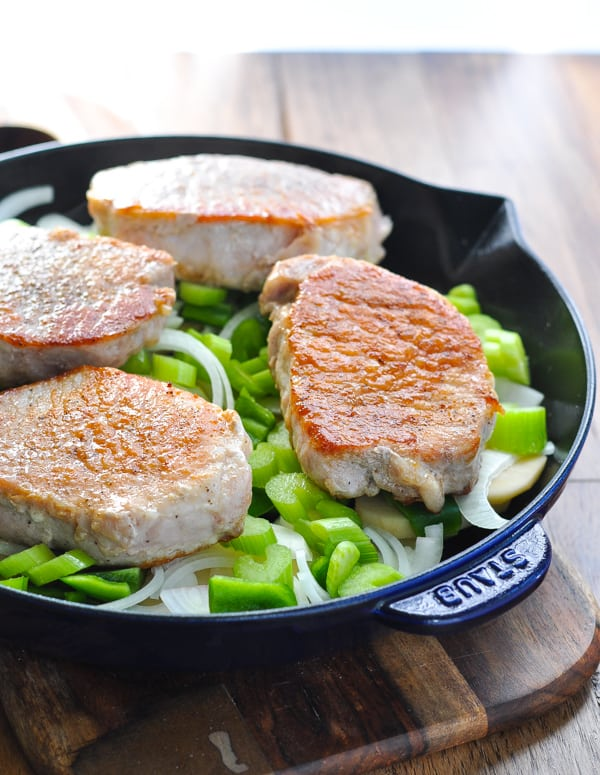 Browned pork chops on top of vegetables in a skillet