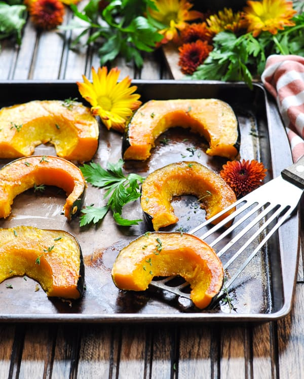 Tray of roasted acorn squash slices with fresh herbs on a spatula