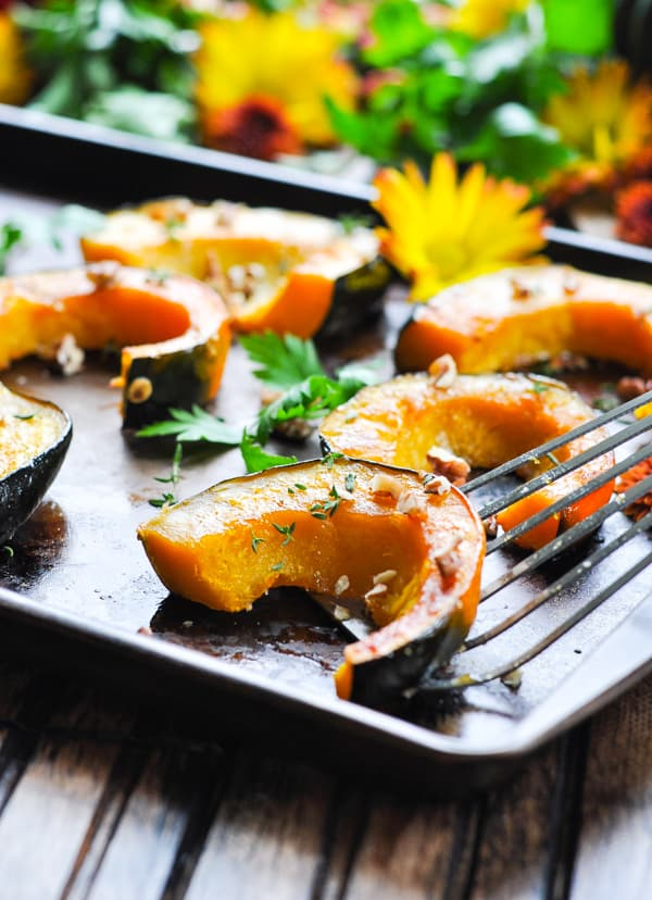 Slices of roasted acorn squash garnished with pecans and herbs
