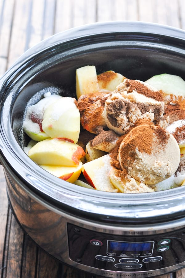 Apples spices and sugar in slow cooker