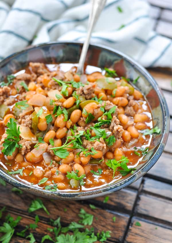 Close up image of a bowl full of slow cooker pork and beans with ground beef