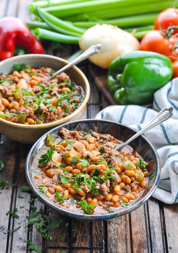 Bowls of slow cooker pork and beans with ground beef garnished with parsley