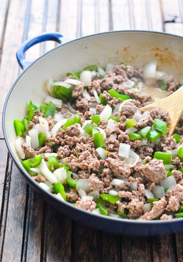 Cooked ground beef with onion and bell peppers in a skillet