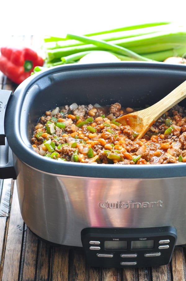 Ingredients for pork and beans in slow cooker with wooden spoon