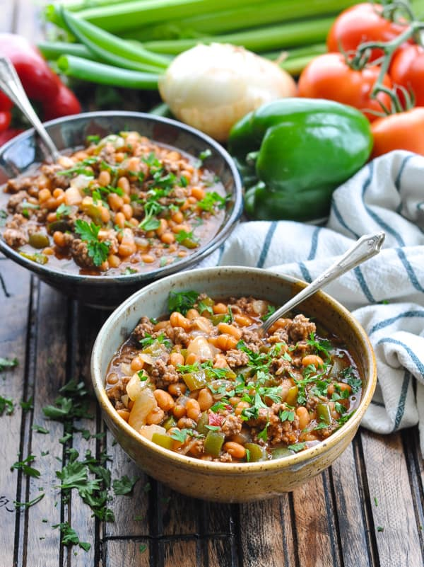 Two bowls of slow cooker pork and beans with ground beef