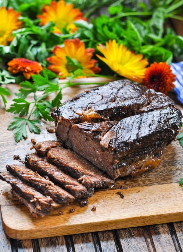 Tender and moist slow cooker roast beef sliced on a cutting board