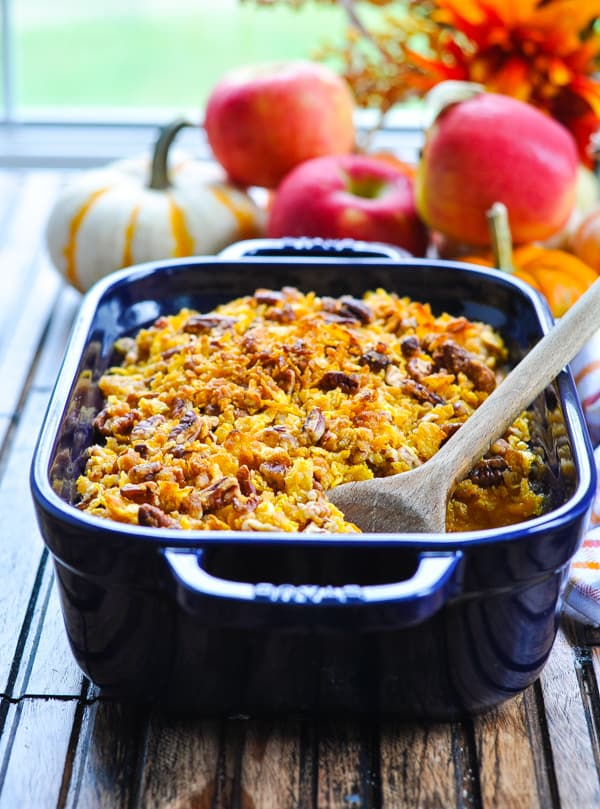 Apple and Butternut Squash Casserole in blue baking dish with wooden spoon.