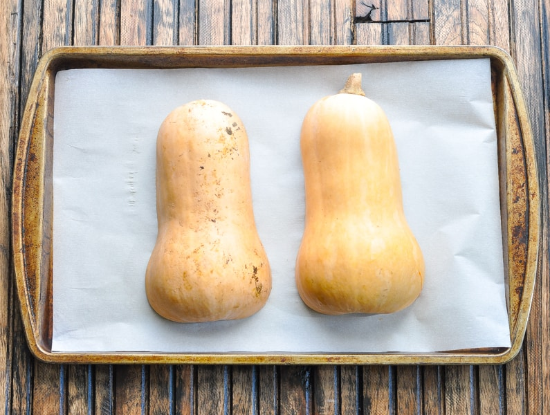 Halved butternut squash on a baking sheet